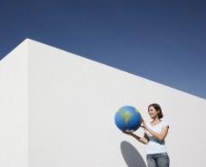 拿着地球模型的女人图片